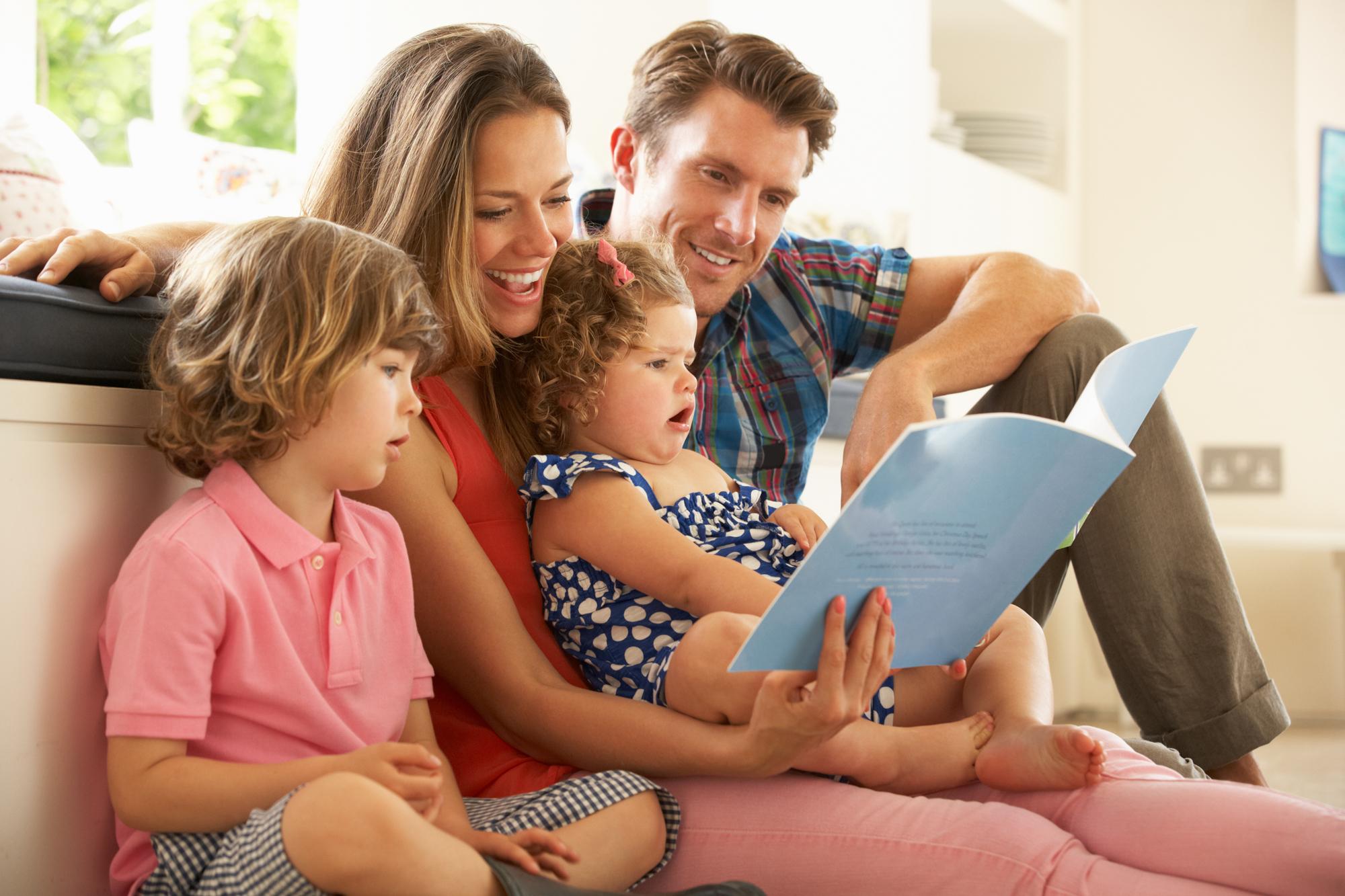 Familie mit zwei Kindern beim Lesen eines Kinderbuches